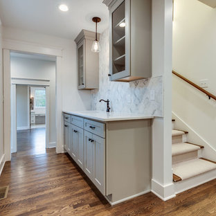 Example of a small country single-wall medium tone wood floor and brown floor wet bar design in Nashville with a drop-in sink, shaker cabinets, gray cabinets, quartz countertops, white backsplash, marble backsplash and white countertops