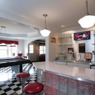アトランタの中くらいのエクレクティックスタイルのおしゃれな着席型バー (クッションフロア、マルチカラーの床、ll型、ドロップインシンク、ガラス扉のキャビネット、テラゾーカウンター、メタルタイルのキッチンパネル) の写真