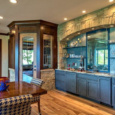 Example of a mid-sized mountain style single-wall light wood floor wet bar design in Other with an undermount sink, recessed-panel cabinets, distressed cabinets, granite countertops, gray backsplash and stone slab backsplash