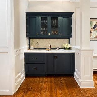 フィラデルフィアのトランジショナルスタイルのおしゃれなウェット バー (珪岩カウンター、無垢フローリング、I型、アンダーカウンターシンク、ガラス扉のキャビネット、青いキャビネット、ベージュキッチンパネル、茶色い床) の写真