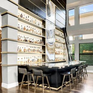 Immagine di un ampio bancone bar minimal con mensole sospese, ante in legno bruno, top in marmo, paraspruzzi bianco, pavimento in legno massello medio, pavimento grigio e top nero