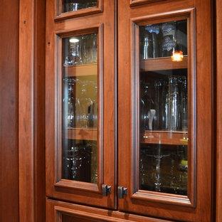 Klassisk inredning av en stor l-formad hemmabar med vask, med luckor med glaspanel och skåp i mellenmörkt trä