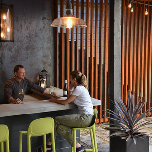 Inspiration for a mid-sized industrial l-shaped seated home bar remodel in San Francisco with concrete countertops