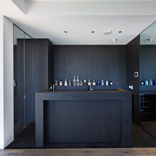 Photo of a modern home bar in Sydney with flat-panel cabinets, dark wood cabinets, black floor and black benchtop.