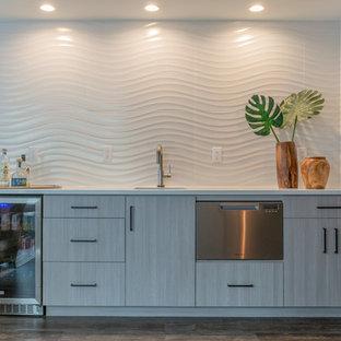デンバーのコンテンポラリースタイルのおしゃれなウェット バー (ラミネートの床、グレーの床、I型、アンダーカウンターシンク、フラットパネル扉のキャビネット、グレーのキャビネット、白いキッチンパネル、白いキッチンカウンター) の写真