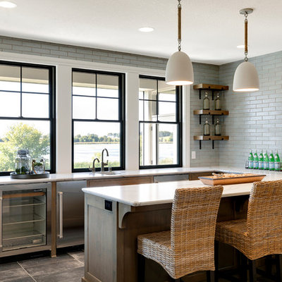 Inspiration for a large coastal u-shaped ceramic tile and brown floor seated home bar remodel in Minneapolis with quartz countertops, gray backsplash, white countertops, an undermount sink and subway tile backsplash