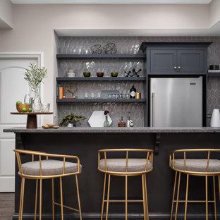 Inredning av en klassisk stor grå parallell grått hemmabar med stolar, med vinylgolv, brunt golv, skåp i shakerstil, grå skåp och grått stänkskydd