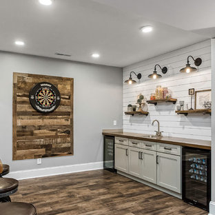 Inspiration for a mid-sized cottage porcelain tile and brown floor seated home bar remodel in Columbus with a drop-in sink, shaker cabinets, white cabinets, wood countertops, white backsplash, wood backsplash and brown countertops