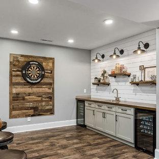 コロンバスの中くらいのカントリー風おしゃれな着席型バー (ドロップインシンク、シェーカースタイル扉のキャビネット、白いキャビネット、木材カウンター、白いキッチンパネル、木材のキッチンパネル、磁器タイルの床、茶色い床、茶色いキッチンカウンター) の写真