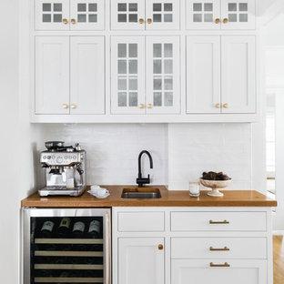 ボストンの小さいトラディショナルスタイルのおしゃれなウェット バー (I型、アンダーカウンターシンク、白いキャビネット、木材カウンター、白いキッチンパネル、淡色無垢フローリング、サブウェイタイルのキッチンパネル、茶色いキッチンカウンター、シェーカースタイル扉のキャビネット) の写真