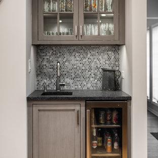 シカゴの小さいトランジショナルスタイルのおしゃれなウェット バー (アンダーカウンターシンク、ガラス扉のキャビネット、中間色木目調キャビネット、グレーのキッチンパネル、茶色い床、黒いキッチンカウンター) の写真