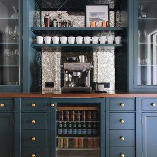 Immagine di un angolo bar classico di medie dimensioni con ante con riquadro incassato, ante blu, top in legno e top marrone
