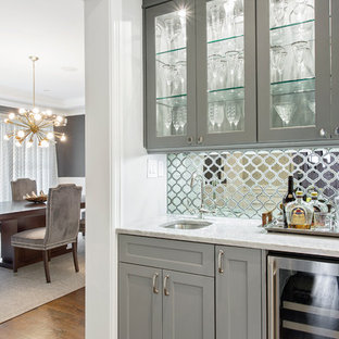 ニューヨークのトランジショナルスタイルのおしゃれなウェット バー (ガラス扉のキャビネット、グレーのキャビネット、大理石カウンター、ミラータイルのキッチンパネル、濃色無垢フローリング、アンダーカウンターシンク、白いキッチンカウンター) の写真