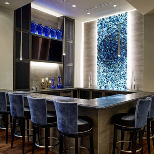 Photo of a contemporary u-shaped home bar in Houston with beige splashback, medium hardwood flooring, brown floors and black worktops.