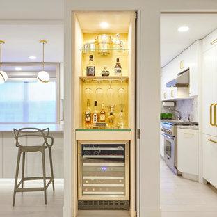 Ispirazione per un piccolo angolo bar contemporaneo con top in vetro e paraspruzzi giallo