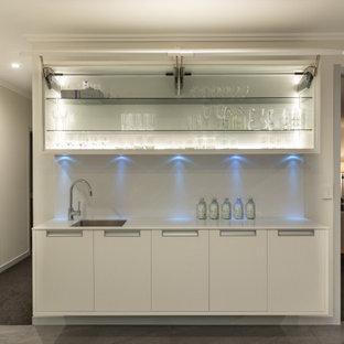 Inspiration pour un bar de salon avec évier linéaire minimaliste de taille moyenne avec un évier posé, un placard à porte plane, des portes de placard blanches, une crédence blanche, un sol en carrelage de céramique, un sol gris et un plan de travail blanc.