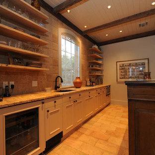 Foto di un armadio bar rustico di medie dimensioni con lavello sottopiano, nessun'anta, ante in legno chiaro, top in granito, paraspruzzi beige, paraspruzzi con piastrelle in terracotta e pavimento in terracotta