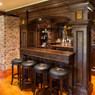 Example of a large classic galley concrete floor and orange floor seated home bar design in Minneapolis with recessed-panel cabinets, dark wood cabinets, wood countertops, mirror backsplash and brown countertops