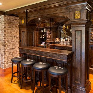 ミネアポリスの広いトラディショナルスタイルのおしゃれな着席型バー (コンクリートの床、ll型、落し込みパネル扉のキャビネット、濃色木目調キャビネット、木材カウンター、オレンジの床、ミラータイルのキッチンパネル、茶色いキッチンカウンター) の写真