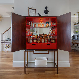 Classic home bar in San Francisco with red cabinets and medium hardwood flooring.