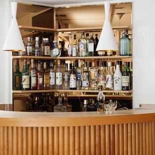 Ispirazione per un bancone bar minimalista di medie dimensioni con lavello sottopiano, nessun'anta, ante in legno chiaro, top in legno, paraspruzzi a specchio, parquet chiaro, pavimento marrone e top marrone