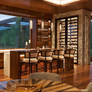 Seated home bar - rustic l-shaped medium tone wood floor and brown floor seated home bar idea in Denver with recessed-panel cabinets, brown cabinets and beige countertops