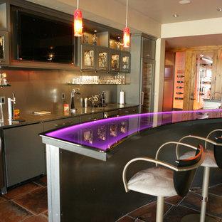 Immagine di un grande armadio bar minimal con lavello da incasso, ante di vetro, ante grigie, top in vetro, pavimento in terracotta e pavimento marrone