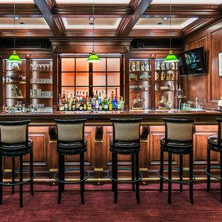 デンバーの広いトラディショナルスタイルのおしゃれな着席型バー (御影石カウンター、木材のキッチンパネル、オープンシェルフ、濃色木目調キャビネット、カーペット敷き、赤い床) の写真