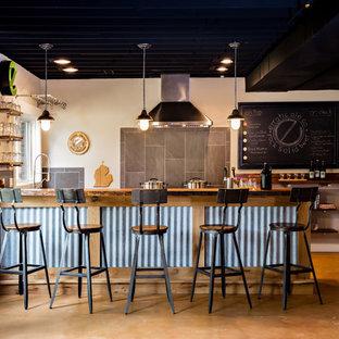 デトロイトの広いインダストリアルスタイルのおしゃれな着席型バー (L型、中間色木目調キャビネット、木材カウンター、コンクリートの床、茶色いキッチンカウンター、グレーのキッチンパネル、オレンジの床) の写真