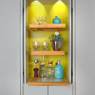 トロントのモダンスタイルのおしゃれなホームバー (フラットパネル扉のキャビネット、木材カウンター、黄色いキッチンパネル) の写真