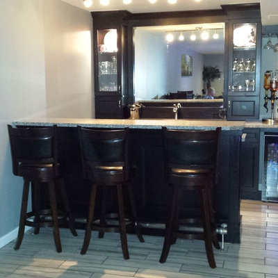 Inspiration for a small contemporary single-wall porcelain tile seated home bar remodel in St Louis with an undermount sink, raised-panel cabinets, black cabinets and granite countertops