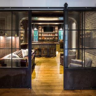 Ejemplo de bar en casa con fregadero tradicional, grande, con armarios con paneles lisos, puertas de armario con efecto envejecido, suelo de madera en tonos medios y encimeras marrones