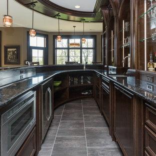 Immagine di un grande bancone bar classico con lavello da incasso, ante con bugna sagomata, ante in legno bruno, top in granito e pavimento in gres porcellanato