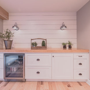 Mid-sized country single-wall wet bar in Detroit with no sink, shaker cabinets, white cabinets, wood benchtops, white splashback, timber splashback, light hardwood floors and beige floor.