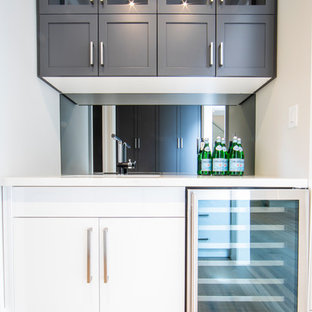 Large traditional l-shaped home bar in Toronto with shaker cabinets, grey cabinets, marble worktops, multi-coloured splashback, mosaic tiled splashback, light hardwood flooring, brown floors and white worktops.