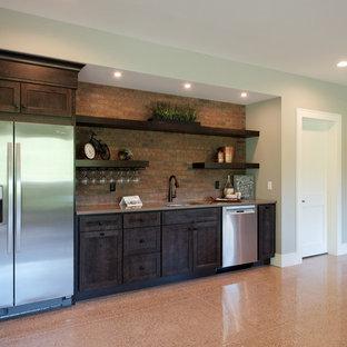 グランドラピッズの広いおしゃれなウェット バー (I型、アンダーカウンターシンク、落し込みパネル扉のキャビネット、濃色木目調キャビネット、クオーツストーンカウンター、赤いキッチンパネル、レンガのキッチンパネル、コンクリートの床、茶色い床) の写真