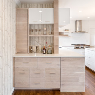 This is an example of a small contemporary home bar in Portland with light wood cabinets and white benchtop.