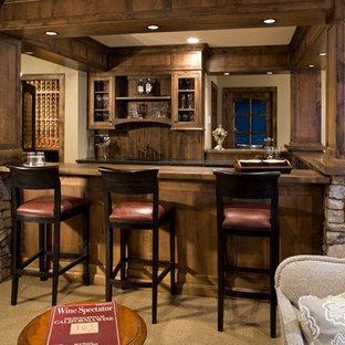 Esempio di un bancone bar rustico con moquette, lavello sottopiano, ante di vetro e ante in legno bruno