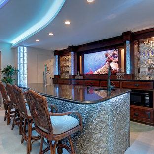 アトランタの中くらいのビーチスタイルのおしゃれな着席型バー (コンクリートの床、ll型、アンダーカウンターシンク、ガラス扉のキャビネット、濃色木目調キャビネット、御影石カウンター、青い床) の写真