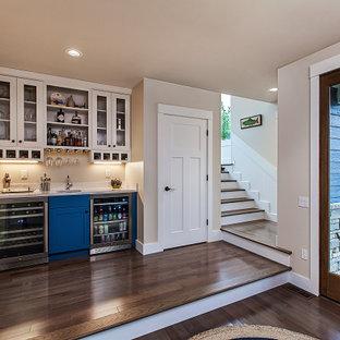 Cette image montre un petit bar de salon avec évier linéaire marin avec un évier encastré, des portes de placard bleues, un plan de travail en quartz, un plan de travail blanc, un placard à porte shaker, un sol en bois foncé et un sol marron.