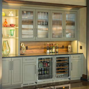 This is an example of a large traditional home bar in Chicago with grey cabinets, granite worktops, brown splashback, ceramic splashback, concrete flooring, brown floors and glass-front cabinets.