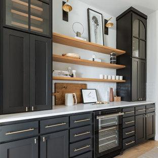 ダラスの中くらいのモダンスタイルのおしゃれなホームバー (ll型、シンクなし、シェーカースタイル扉のキャビネット、黒いキャビネット、白いキッチンパネル、淡色無垢フローリング、白いキッチンカウンター) の写真