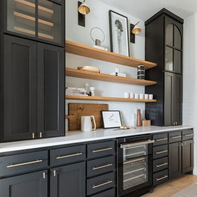 Mid-sized minimalist galley light wood floor home bar photo in Dallas with no sink, shaker cabinets, black cabinets, white backsplash and white countertops