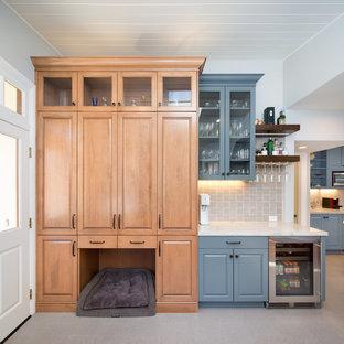 Diseño de bar en casa lineal, tradicional, de tamaño medio, sin pila, con armarios tipo vitrina, puertas de armario azules, salpicadero verde, suelo gris y encimeras blancas
