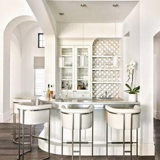 Ispirazione per un bancone bar mediterraneo con ante di vetro, ante bianche, parquet scuro, pavimento marrone e top grigio