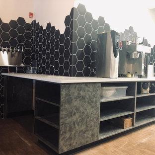Idee per un grande bancone bar industriale con lavello da incasso, nessun'anta, ante grigie, top in onice, paraspruzzi nero, paraspruzzi con piastrelle in ceramica, pavimento marrone, top bianco e pavimento con piastrelle in ceramica