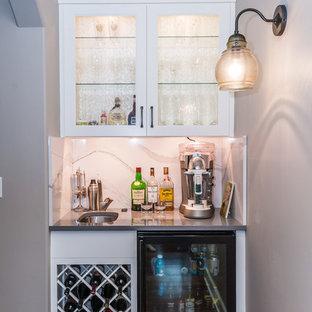 Immagine di un piccolo angolo bar con lavandino classico con lavello sottopiano, ante di vetro, ante bianche, top in superficie solida, paraspruzzi bianco, paraspruzzi in lastra di pietra, parquet scuro e pavimento marrone