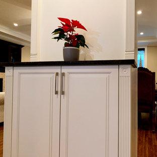 バンクーバーの中くらいのおしゃれなバーカート (ll型、ドロップインシンク、白いキャビネット、木材カウンター、白いキッチンパネル、木材のキッチンパネル、合板フローリング、白い床、白いキッチンカウンター) の写真