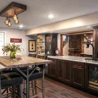 Idee per un bancone bar classico di medie dimensioni con ante in legno bruno, top in granito, pavimento marrone, top multicolore, paraspruzzi con lastra di vetro e parquet scuro