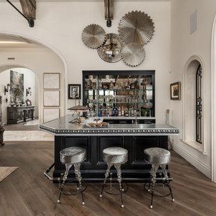 Cette photo montre un très grand bar de salon romantique en L avec des tabourets, un évier posé, un placard sans porte, des portes de placard noires, un plan de travail en zinc, une crédence multicolore, une crédence en carreau de miroir, un sol en bois brun, un sol marron et un plan de travail gris.
